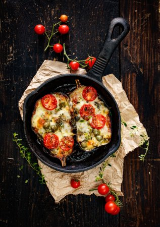 Photo for Baked eggplant stuffed with tomatoes, peppers, capers, garlic and mozzarella cheese with  addition aromatic herbs - Royalty Free Image
