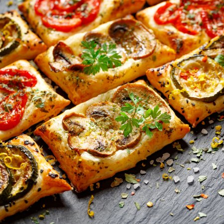 Small vegetable tarts with puff pastry, tomato, mushrooms and zucchini. Delicious vegetarian appetizers