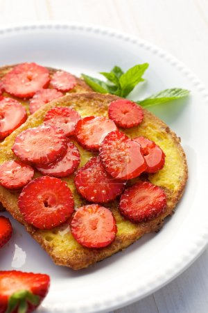 French toasts with fresh strawberries on white plate