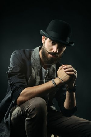The bearded man in a bowler hat clenched his hands into the lock
