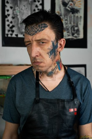 Tattooed man in leather apron making faces