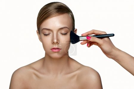 Woman applying Powder Foundation with Brush.