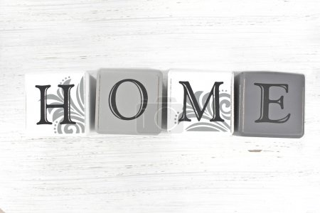 Home spelled with blocks on a distressed wood background