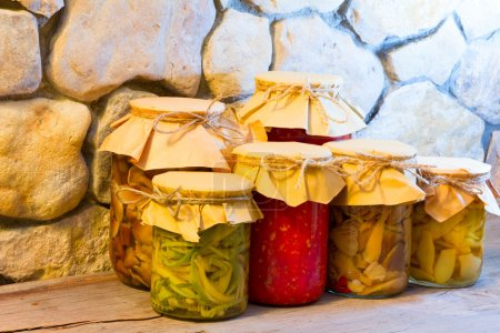 Photo for Home canned vegetables in glass jars near the stone wall.  Pickled ramsons, mushrooms, green beans, tomato sauce. The concept of natural product preparations for the winter in a rustic style. - Royalty Free Image