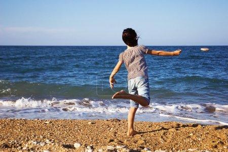 Foto de Niño que lanza una roca en la playa - Imagen libre de derechos