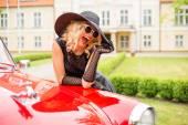 """Постер, картина, фотообои """"Гламурная женщина, опираясь на красный ретро автомобиль"""""""