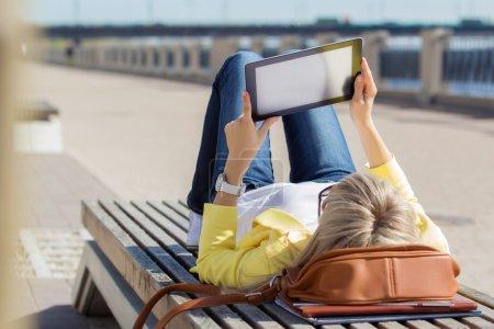 Photo pour Femme utilisant un ordinateur tablette à l'extérieur - image libre de droit