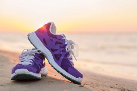 Photo for Pair of colorful  running shoes on the beach at sunset - Royalty Free Image