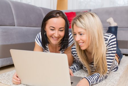 Two young women using computer while lying down on floor in living room