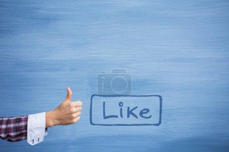 Photo pour Main affichant des pouces vers le haut du geste avec comme le mot sur le fond bleu - image libre de droit