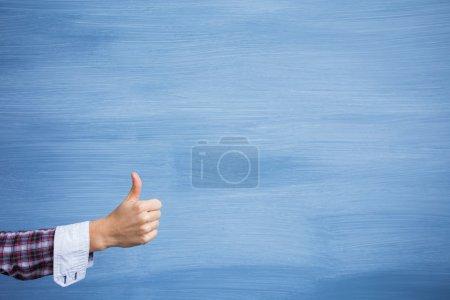 Photo pour Main, montrant les pouces vers le haut de geste sur fond bleu - image libre de droit