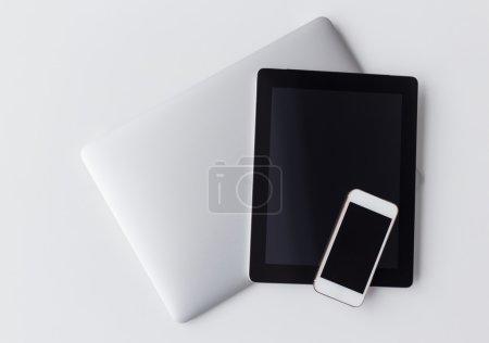 Foto de Modern technology gadgets on white table, phone. tablet and pc - Imagen libre de derechos