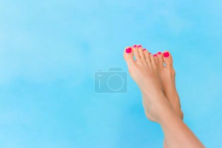 Bare woman feet over blue swimming pool water