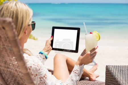 Young woman relaxing on a beach with cocktail and tablet