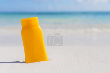 Sunscreen bottle on sand at the beach