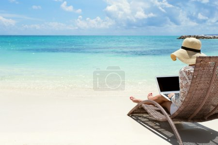 Business woman using laptop computer on the beach