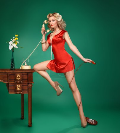 Pin-up girl in red dress talking on vintage phone