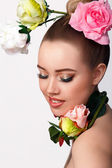 Fashion Beauty Model Girl with Rose Flowers Hair. Make up and Hair Style. Hairstyle.Bouquet of Beautiful Flowers on ladys head