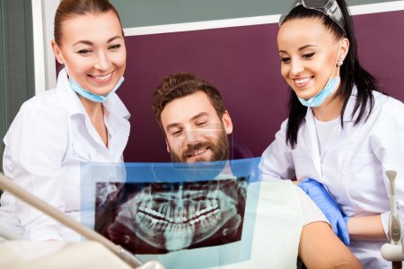 Photo for Smiling female doctor and her assistant showing teeth x-ray to male patient in dental hospital. Handsome male patient sitting in chair smilling with straight white teeth and looking at dental x-ray. - Royalty Free Image