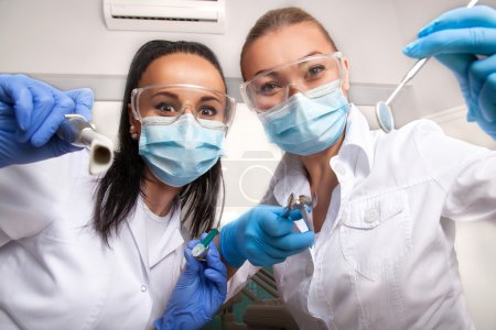 Female doctor dentist and assistant in masks looking at camera