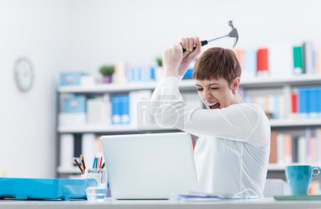 Photo for Stressed woman screaming and destroying her laptop with an hammer, computer problems and overwork concept - Royalty Free Image