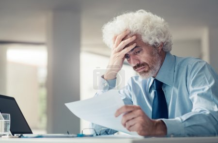 Confused businessman receiving bad news