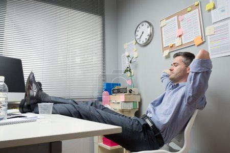 Photo pour Lazy office worker feet up relaxing in his small office. - image libre de droit