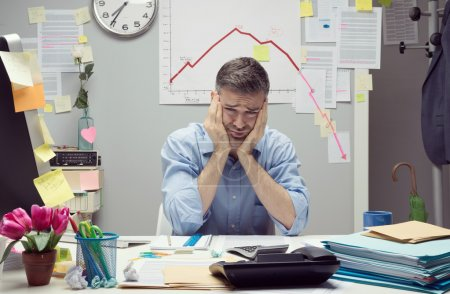 Photo for Desperate businessman at desk with negative business chart on background. - Royalty Free Image