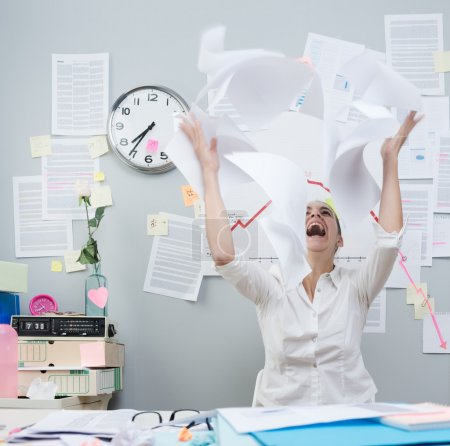 Photo for Angry businesswoman in office throwing paperwork in air and shouting. - Royalty Free Image