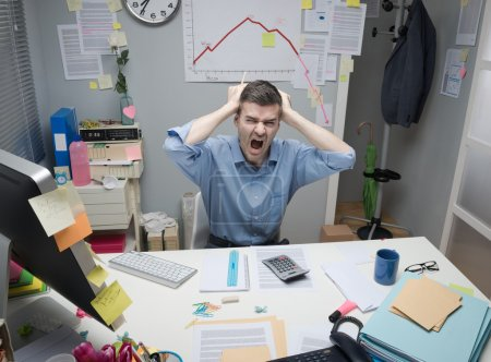 Photo for Desperate businessman screaming with head in hands and negative business chart on background. - Royalty Free Image