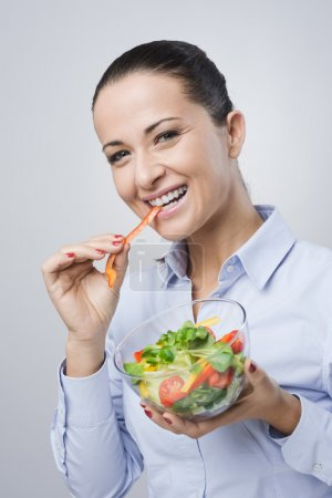 Photo for Cheerful woman eating salad and smiling, healthy eating concept - Royalty Free Image