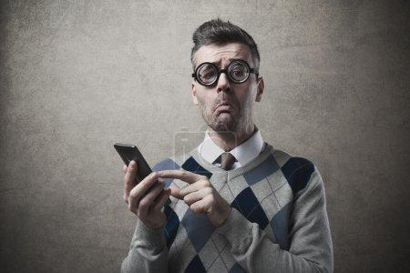 Photo pour Drôle de débile désemparé ayant des problèmes avec son smartphone - image libre de droit