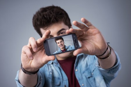 Teenager taking selfies with his smartphone