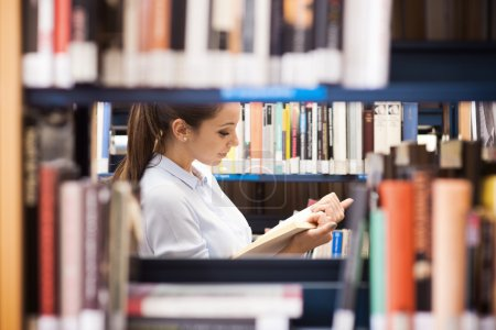 Photo for Young smiling student at the library searching for books - Royalty Free Image