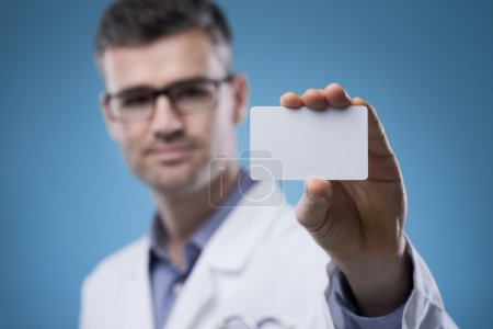 Smiling doctor with business card