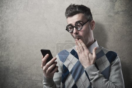 Photo for Funny guy having troubles with his smartphone, hand over mouth - Royalty Free Image