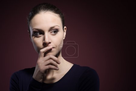 Photo for Pensive young woman posing with hand on chin - Royalty Free Image