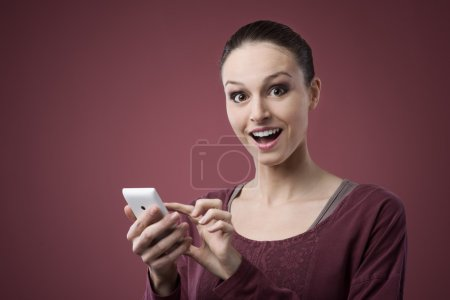 Photo for Surprised young woman with wide open eyes using mobile phone - Royalty Free Image