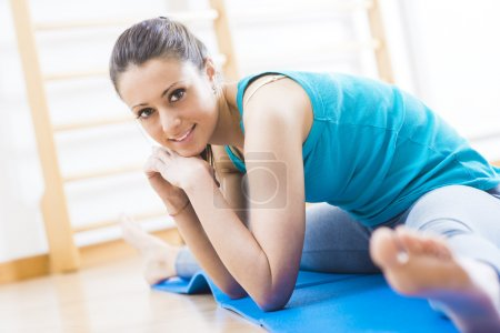 Attractive woman doing stretching exercises at gym