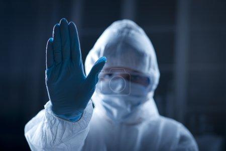Female scientist in protective hazmat suit with hand raised