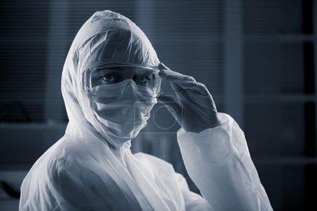 Photo pour Chercheur portant une combinaison de protection contre les dangers et des lunettes de sécurité . - image libre de droit