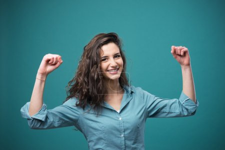 Photo for Cheerful young woman smiling with raised fists - Royalty Free Image