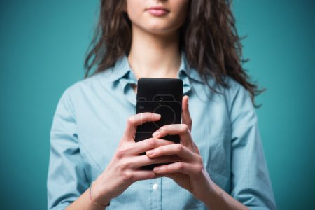 Photo for Young teenager girl typing and messaging on her smartphone - Royalty Free Image