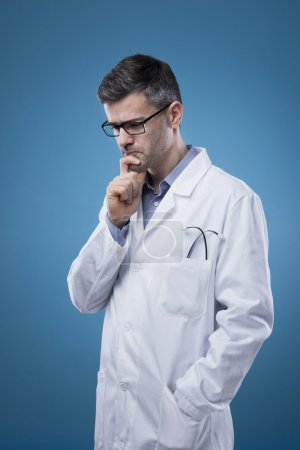Pensive doctor with hand on chin