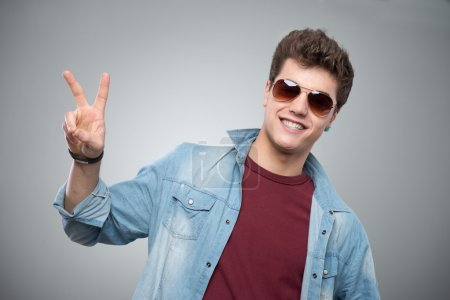 Photo for Cheerful cool guy in sunglasses making V sign on gray background - Royalty Free Image