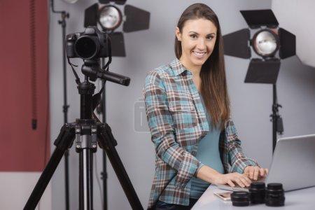 Photo pour Femme photographe travaille dans son studio de photo professionnel avec un ordinateur portable, la caméra et le matériel d'éclairage - image libre de droit
