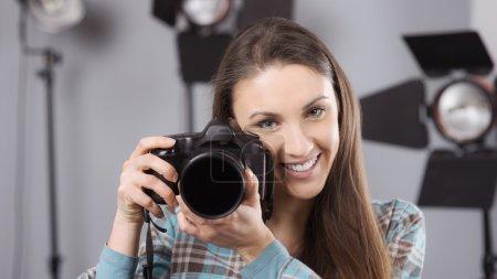 Photo pour Jeune photographe posant dans son studio professionnel, tenant un appareil photo numérique avec un équipement d'éclairage en arrière-plan - image libre de droit