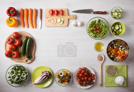 Photo for Healthy eating concept with fresh vegetables and salad bowls on kitchen wooden worktop, copy space at center, top view - Royalty Free Image