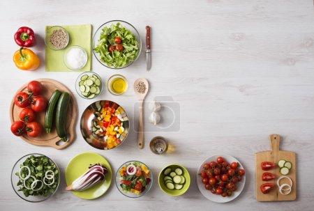 Photo pour Concept de restauration saine avec légumes frais et saladiers sur plan de travail en bois cuisine, espace copie à droite, en haut de la page vue - image libre de droit