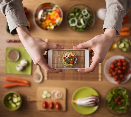 Photo for Man holding a smart phone hands close up, kitchen table worktop on background with fresh vegetables and utensils - Royalty Free Image